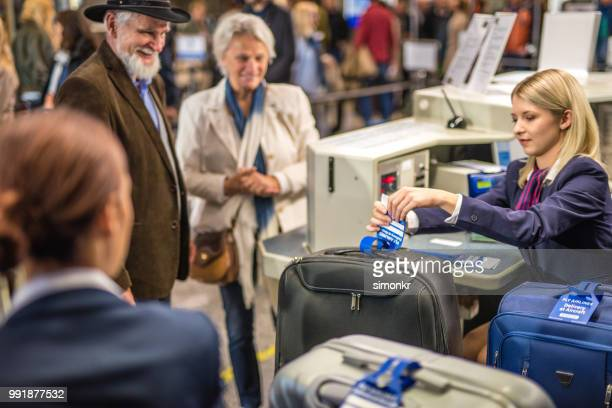 Service staff putting label to luggage at airport