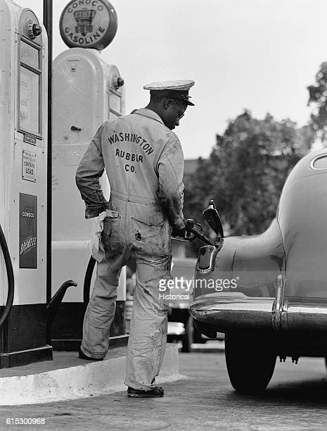 A service station attendant fills an automobile with gas prior to the beginning of rationing Washington DC May 14 1942