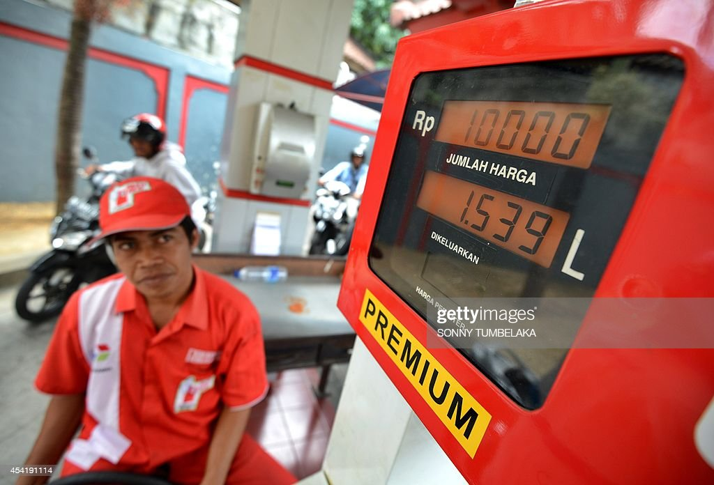 A service station attendant looks at the pump as Indonesian motorists queue up for gasoline in Denpasar on the Indonesian tourist island of Bali on August 26, 2014 as major cities across the country are hit with a shortage of subsidized fuel forcing long lines and the closure of service stations. Economists say Indonesia must phase out the huge fuel subsidies that make petrol prices in Indonesian among the cheapest in Asia but gobble up about 20 percent of the state budget. The subsidies are historically a tense political issue in Indonesia, where fuel price hikes to reduce the payouts have been met with massive protests and caused divisions between coalition partners in government.