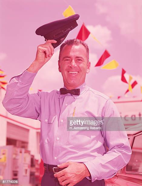 Service station attendant smiling and lifting hat in greeting gesture. (Photo by H. Armstrong Roberts/Retrofile/Getty Images)
