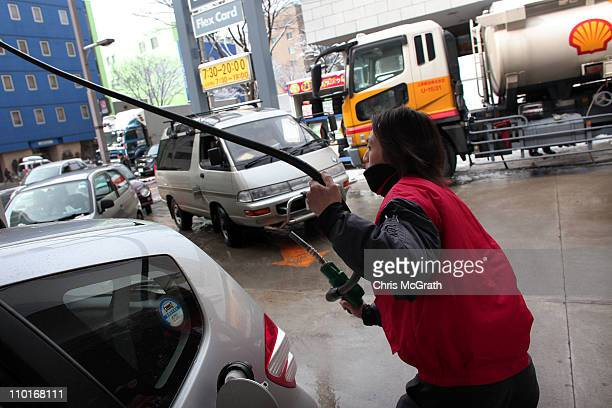 Service station attendants usher in cars for gas at a Shell service station after the earthquake and tsunami on March 16 2011 in Aomori Japan Many...