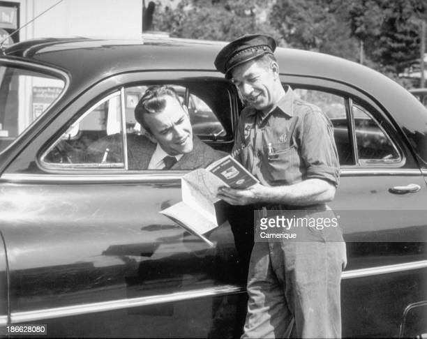 Service station man with a map showing directions to man in car 1945