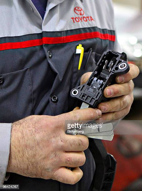 Service technician Frank Russo uses a feeler gauge to determine the proper steel plate to insert into the accelerator assembly of a recalled 2007...