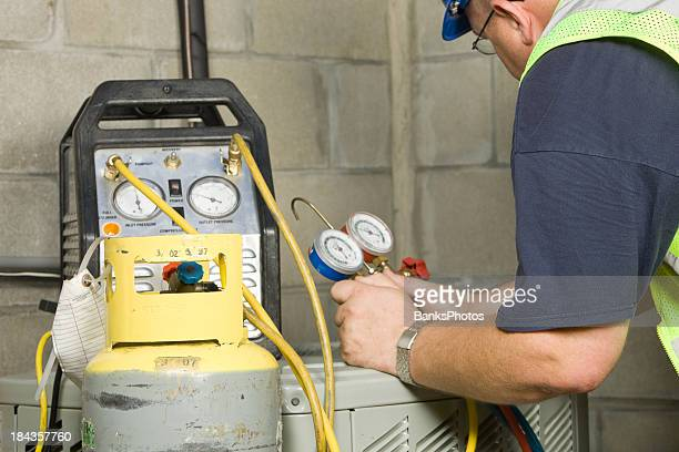 Service Technician Recovers Refrigerant from Air Conditioner System