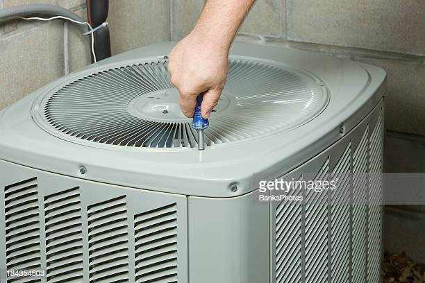 Service Technician Removing or Installing Air Conditioner Fan Cover