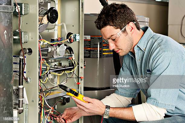 service technician testing a furnace. - hvac stock photos and pictures