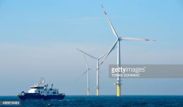 A service vessel makes its way past wind turbines run by Germany's biggest power supplier Eon at the offshore wind farm Amrumbank West near the North...