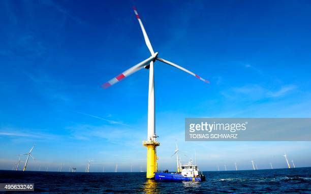 A service vessel picks up workers from a wind turbine of the German offshore wind farm 'Amrum Bank West' owned by German energy company EON are seen...