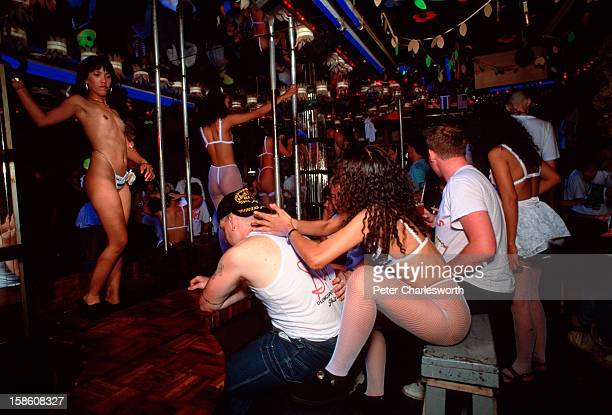 Serviceman gets a massage from a 'bar girl' while his friends drink and play in the Caligular Bar with sex workers dancing topless on stage The bar...