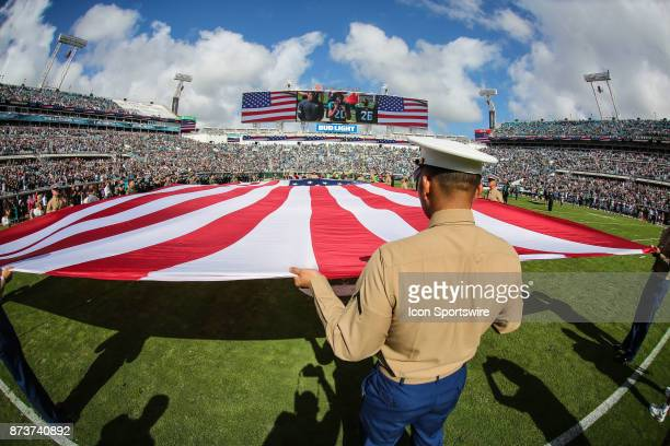A serviceman holds the US Flag during the National Anthem during the game between the Los Angeles Chargers and the Jacksonville Jaguars on November...
