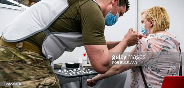 Serviceman injects a dose of Covid-19 vaccine to a woman at the vaccination site in Molenbeke, Arnhem, on May 31, 2021. - Defense is temporarily...