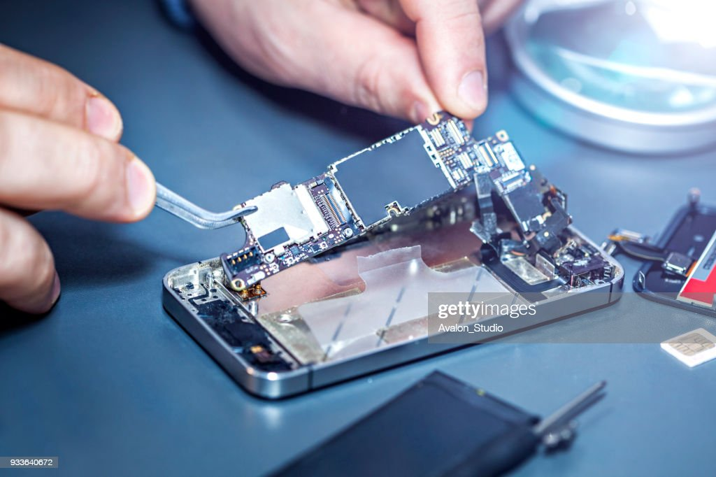 Serviceman is repairing a damaged mobile phone. : Stock Photo
