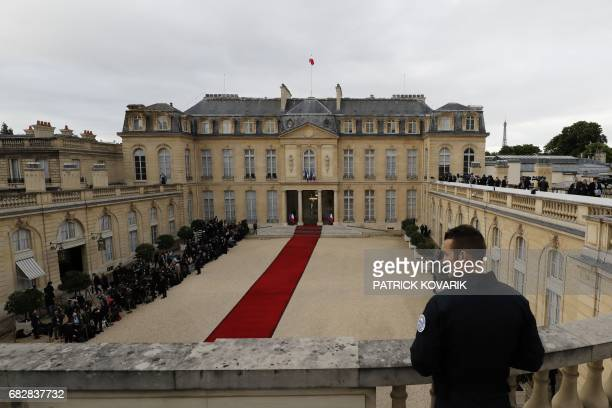 TOPSHOT A serviceman looks at journalists waiting at the entrance of the Elysee presidential Palace to attend Emmanuel Macron's formal inauguration...