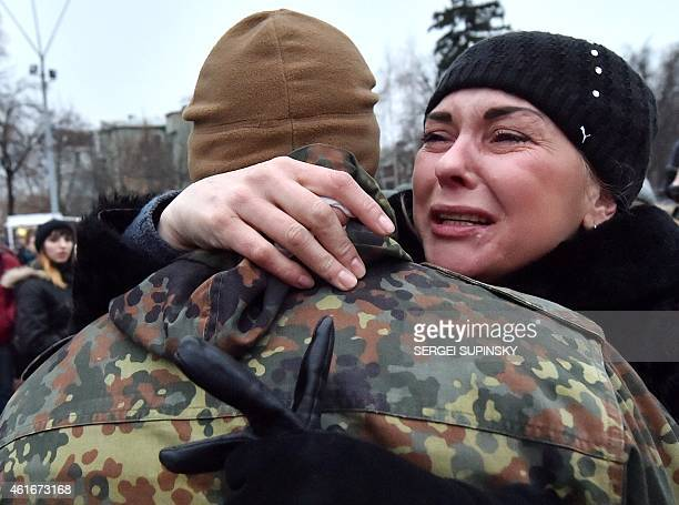 A serviceman of Azov the Ukrainian volunteer battalion holds a relative during a ceremony in Kiev on January 17 2015 before leaving to the east of...