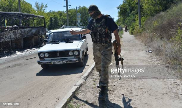 A serviceman of Ukrainian volunteer battalions of territorial defence Lugansk1 checks passing cars at their checkpoint near the eastern Ukrainian...
