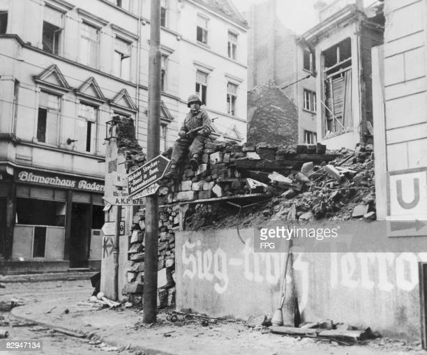 US serviceman Private Jesse W Dolimonte on guard in the newlycaptured German city of Bonn March 1945 On the wall below him is the painted slogan...
