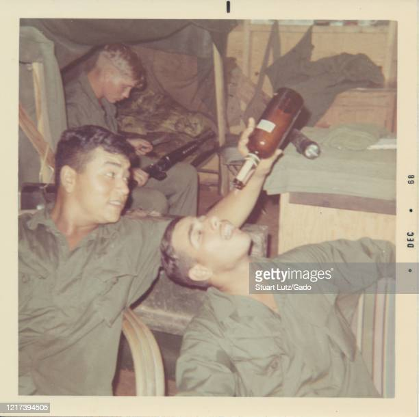 Serviceman sits on a camp bed and cleans a rifle, while a soldier in the foreground tips the dregs from a bottle of alcohol into a colleague's open...