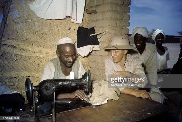 US serviceman talks with local work as he sews garments at the US Army and Airforce base in Khartoum AngloEgyptian Sudan