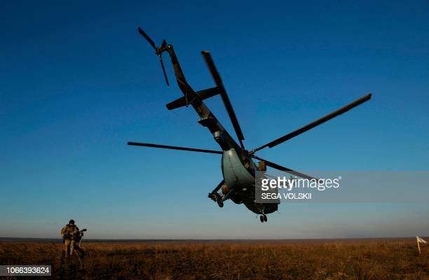 TOPSHOT A serviceman walks near a Ukrainian military helicopter flying during military drills near Urzuf village not far from the city of Mariupol...
