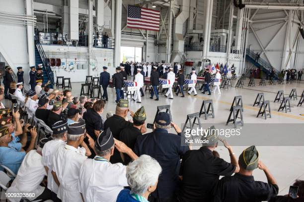 Servicemen and women from many branches of the military salute as military personnel bring in the presumed remains of US soldiers in 55 caskets...