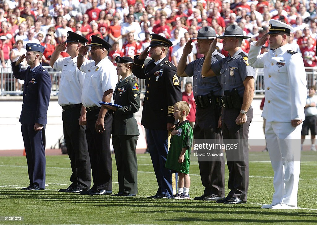 Servicemen and women salute as the flag is lowered to half mast while the Ohio State band plays taps during a September 11 memorial before the game between the Ohio State Buckeyes and the Marshall Thundering Herd on September 11, 2004 at Ohio Stadium in Columbus, Ohio. Ohio State defeated Marshall 24-21.
