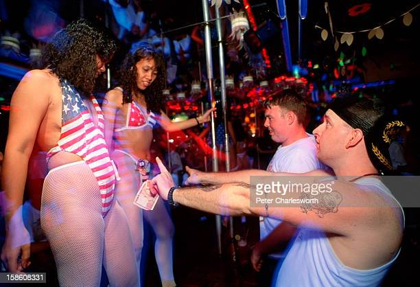 Servicemen interact with sex workers dancing on stage wearing American Flag bikinis They are drinking and playing in the Caligular Bar The bar is a...