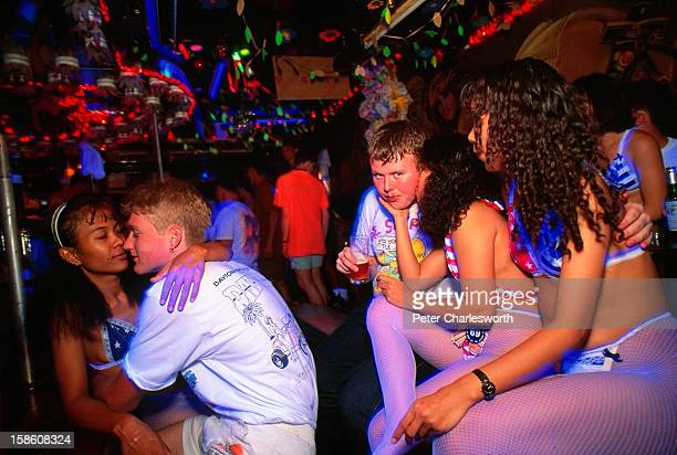Servicemen interact with sex workers wearing American Flag bikinis They are drinking and playing in the Caligular Bar The bar is a GoGo bar in...