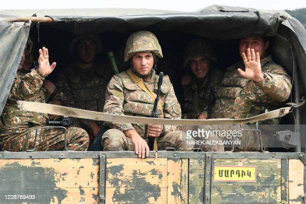 Servicemen of Karabakh's Defence Army wave while riding in the back of a truck on the way to the town of Martakert during fighting with Azerbaijan...