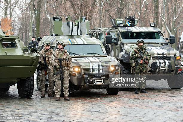 Servicemen of police units and the National Guard of Ukraine stay on the line by their armored cars during the parade prior to the first patrolling...
