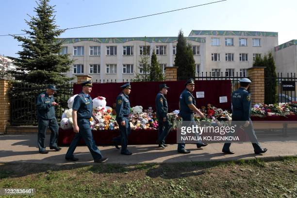 Servicemen of Russia's Emergencies Ministry walk past a makeshift memorial for victims of the shooting at School No. 175 in Kazan on May 12, 2021. -...