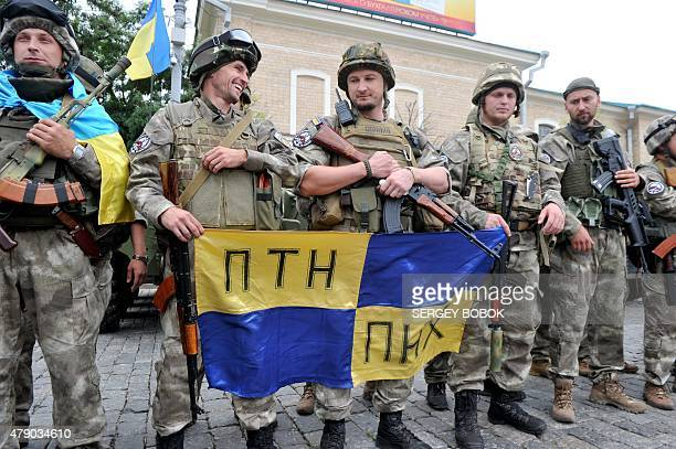 Servicemen of the Eastern Corps Special company of the Ukrainian Ministry of Internal Affairs hold the flag bearing offensive abbreviations for...