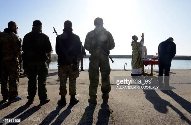 Servicemen of the proUkrainian St Maria battalion attend a Sunday prayer on their base near the eastern Ukrainain city of Mariupol on October 12 2014...