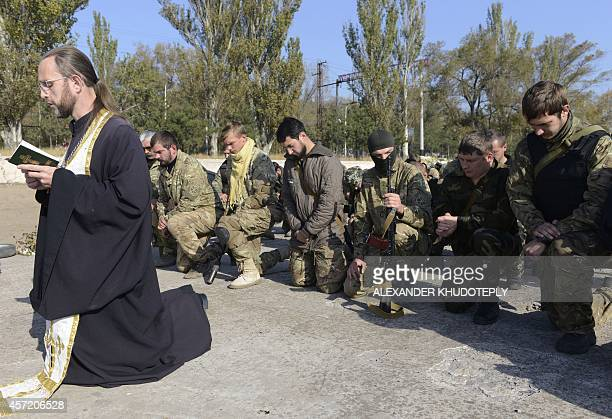 Servicemen of the Ukrainain St Maria battalion attend a prayer on their base in Mariupol eastern Ukraine on October 14 2014 to mark a religious...
