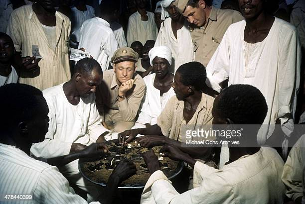 US servicemen watch as the local men play a regional board game at the US Army and Air Force base in Khartoum AngloEgyptian Sudan
