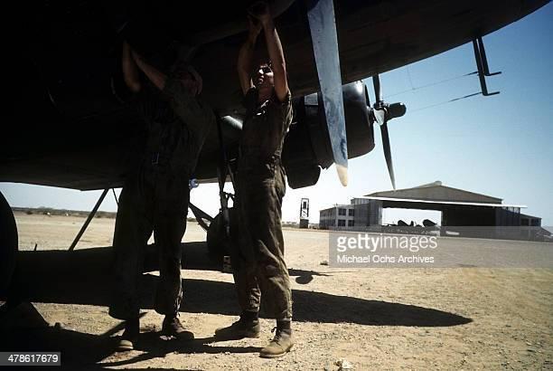 US servicemen work on a B24 Liberator plane at the Wadi Seidna air strip at the US Army Air Force/Royal Air Force base in Khartoum AngloEgyptian Sudan