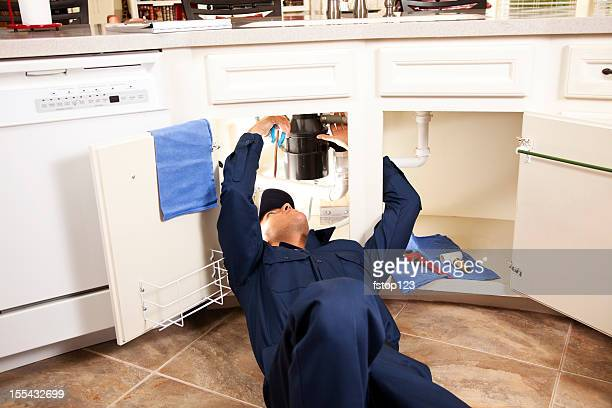 Services Industry:  Plumber working under sink in kitchen.