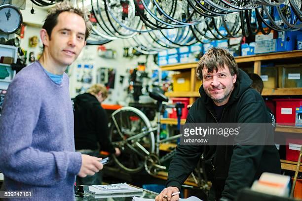 Servant un client, magasin de vélos, regardant à la caméra