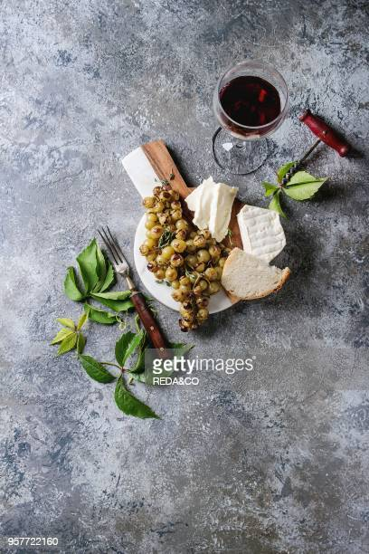 Serving board with sliced camembert cheese and baked bunch of green grapes served with bread glass of red wine corkscrew green leaves fork over gray...