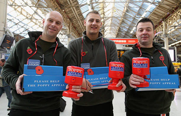 Serving British Army soldiers and recording artists Gary Chilton Ryan Idzi and Richie Maddocks of The Soldiers distribute poppies for the Poppy...