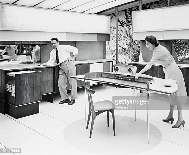 A serving cart that walks to the table loads scrapes washes dries and stores dishes emerges from its cupboard at left in this RCA Whirlpool Miracle...