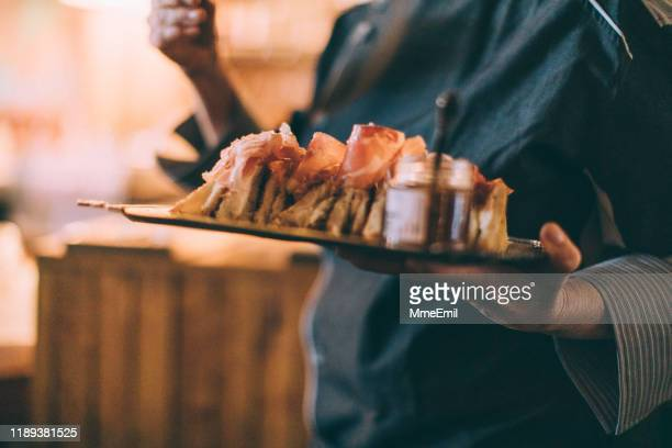 serving cheese sandwich during a party - mmeemil stock photos and pictures