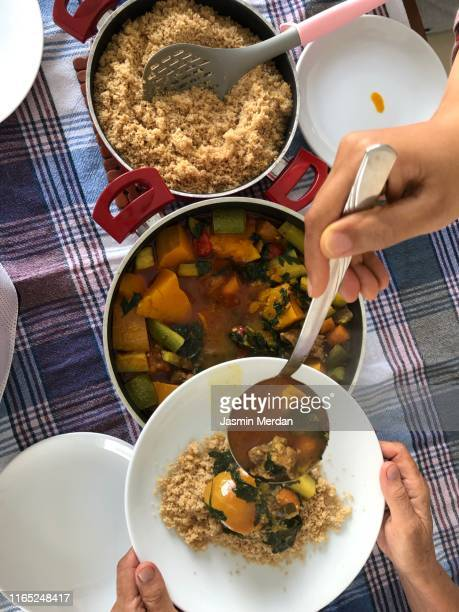 serving cuscus and vegetable lunch on table at home - couscous photos et images de collection
