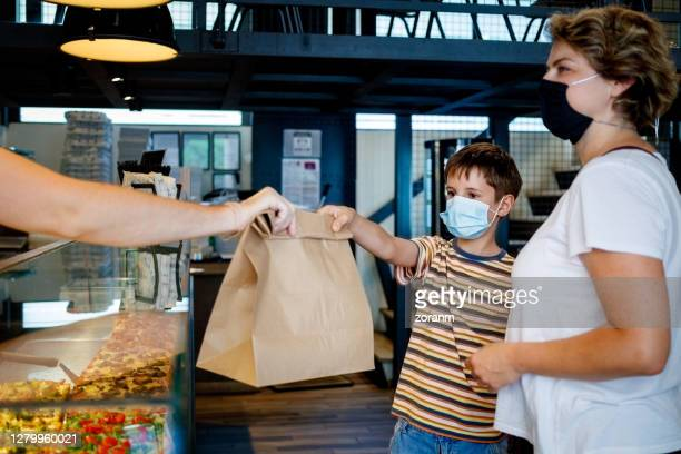 serving customers amid covid-19 pandemic era - lunch bag stock pictures, royalty-free photos & images