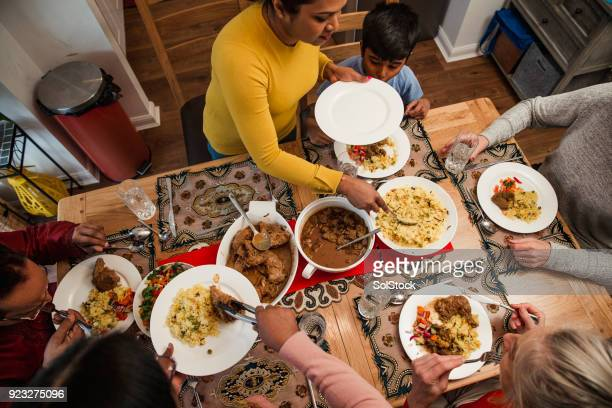serving dinner to her family - ramadan stock pictures, royalty-free photos & images