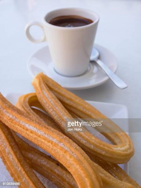a serving of churros and cup of chocolate in a plaza mayor restaurant. - churro fotografías e imágenes de stock