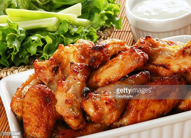 Serving of crispy chicken wings and salad