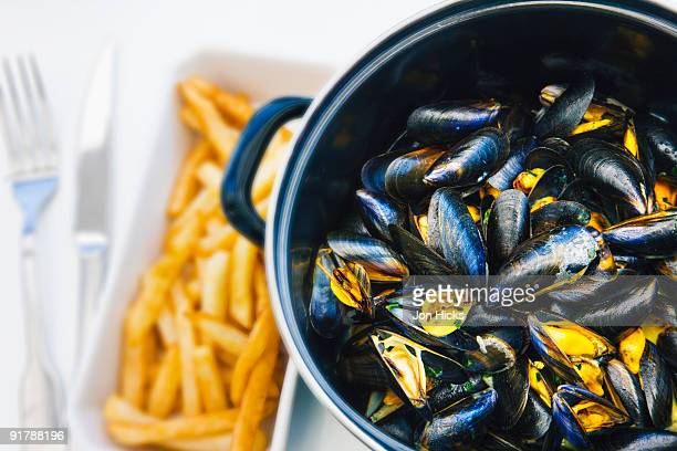 A serving of mussels with chips.