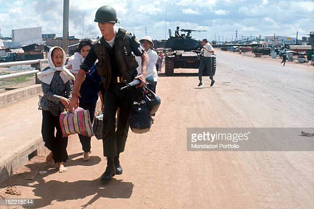 A serving officer from the South Vietnamese coalition carrying some bags for a fleeing Vietnamese family in the background in the centre an armoured...