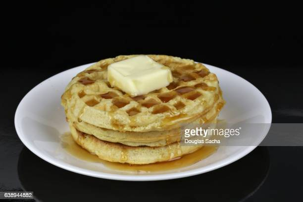Serving plate of Waffles topped with Butter and maple syrup