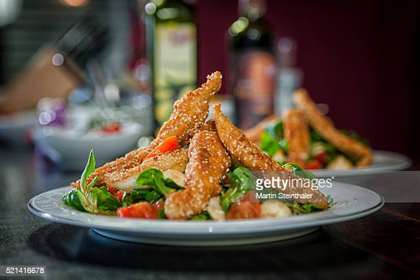 Sesam fried chicken on fresh salad decorated on a plate